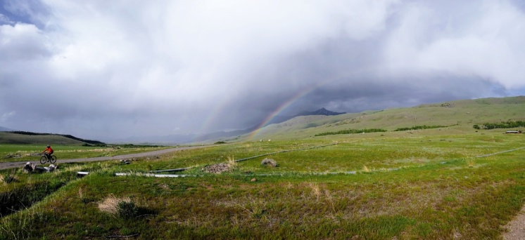 Mo rides back to camp being chased by a storm ... and a double rainbow