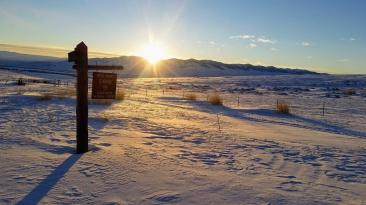 The sun over the mountains while the shadows grow shorter.
