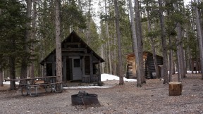 The cabin, woodshed, and outhouse