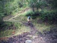 Riding the Turner he surveys a line through the mud.